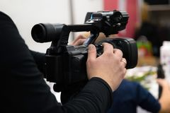 Covering an event with a video camera. Videographer films with video camera. Camera operator working indoors royalty free stock photos