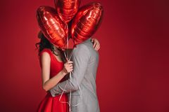 Covering faces with bundle of balloons isolated on red royalty free stock photography