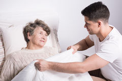 Covering grandmother with blanket Stock Images