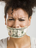 Covering mouth with a dollar banknote Stock Images