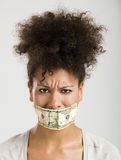 Covering mouth with a dollar banknote Royalty Free Stock Photos