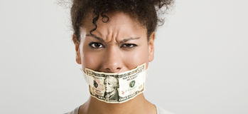 Covering mouth with a dollar banknote Stock Image