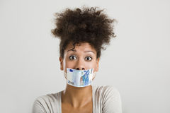 Covering mouth with a euro banknote Royalty Free Stock Image