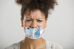 Covering mouth with a euro banknote Stock Photo