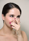 Covering nose with fingers. Beauty shot of a young woman covering her face with fingers and smiling Stock Photography