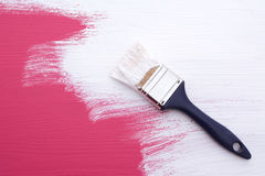 Covering pink paint with a coat of white emulsion. Covering pink paint on wooden board with a paintbrush with a coat of white emulsion stock photos