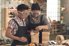Covering with protective lacquer. Father and son in goggles covering little stool with lacquer Stock Photography