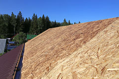 Covering the roof of a metal tile. Covering the roof of a wooden house a metal tile stock image