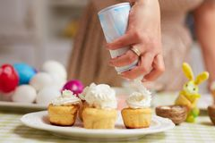 Covering small Easter cakes with cream for the Easter table in t royalty free stock photo