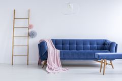 Coverlet on the couch. Pink coverlet thrown on the blue comfy couch in room with wooden ladder and empty white wall Stock Photo