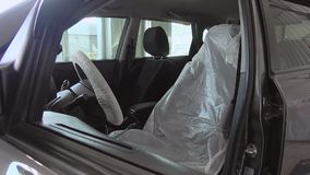 Covers for protection from dirt in the car. Car repair and maintenance. Covers to protect the seat and steering from dirt in the car. Repair and maintenance of stock video footage