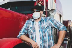 Free Covid-19 Impacting The Transportation  Industry Concept With Truck Driver Wearing Safety Face Mask Next To Big Rig. Confident Truc Stock Images - 181721874