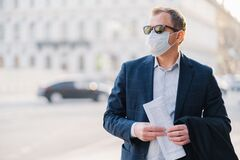 Free Covid-19. Man Worker Dressed In Formal Wear, Holds Newspaper In Hands, Poses At Street, Wears Surgical Mask, Avoids Crowded Street Royalty Free Stock Photos - 177384358