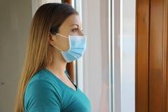 Free COVID-19 Pandemic Coronavirus Woman Mask Looking Through The Window Home Quarantine For Disease Virus SARS-CoV-2. Girl Looking Stock Image - 178567481