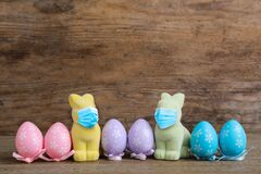 Free COVID-19 Pandemic. Easter Bunnies In Protective Mask And Colorful Eggs On Wooden Background Stock Images - 207465934
