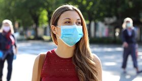 Free COVID-19 Social Distancing Woman In City Street Wearing Surgical Mask Against Disease Virus SARS-CoV-2. Girl With Face Mask Walks Stock Images - 181702984