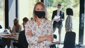 COVID-19 as new normal. Portrait of young happy gen-z 20s blonde business woman in face mask at light office slow motion