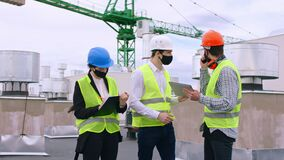 COVID-19 construction site group of specialists engineers architect analyzing the plan of construction discussing some