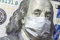 COVID-19 coronavirus in USA, 100 dollar money bill with face mask. COVID-19 affects global stock market. World economy hit by corona virus outbreak and