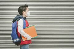 Covid-19,kid with medical mask and backpack who walks to school