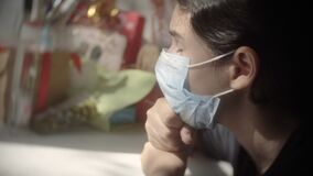 Covid 19. little girl looks out the window sad in a medical gauze mask. self-isolation concept virus coronavirus