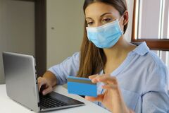 COVID-19 Pandemic Coronavirus E-commerce Mask Girl Buying with Laptop. Young woman with mask buying online with credit card during