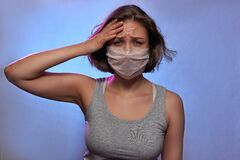 COVID-19 Pandemic Coronavirus. Girl with protective mask on face feels sick. Woman isolated on background in studio