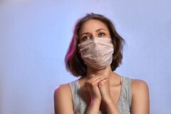 COVID-19 Pandemic Coronavirus. Girl with protective mask on face. Woman isolated on the light background in studio