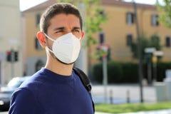 COVID-19 Pandemic Coronavirus Man in city street wearing KN95 FFP2 face mask protective for spreading of Coronavirus Disease 2019