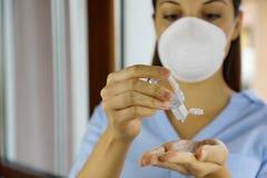 COVID-19 Pandemic Coronavirus mask woman nurse wash hand sanitizer gel dispenser, against Novel coronavirus 2019-nCoV. Home