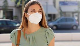 COVID-19 Pandemic Coronavirus Woman in city street wearing KN95 FFP2 mask protective for spreading of disease virus SARS-CoV-2.