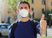 COVID-19 Positive young man wearing protective mask KN95 FFP2 avoiding Coronavirus disease 2019 showing thumbs up in city street