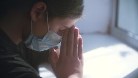 Covid 19 religion concept. little girl looks out the window sad in a medical gauze mask. faith and religion doomsday