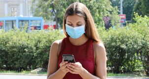 COVID-19 Woman wearing  protective mask using smart phone in city street