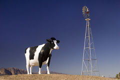 Cow. A larger than life cow statue and windmill Stock Images