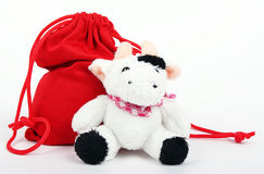 Cow And Bag With Gifts. The cow sits near to a bag with gifts 2009 Stock Photo