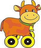 Cow with bell on green strap, toy on wheels Royalty Free Stock Images