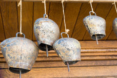 Cow-bells hanging on a wooden beam Stock Photos