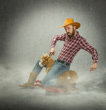 Cow boy riding a fake child horse Stock Photos
