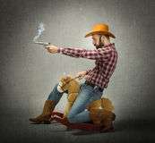 Cow boy riding horse and shot with gun Stock Photos