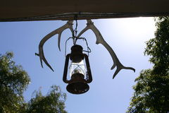 Cow camp. Old lamp and old horns hanging stock image