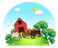 A cow and a carriage in front of a barn in the farm Royalty Free Stock Image