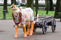 A cow with a cart. Painted plaster cast of a cow in a smart hat and a cart in the park and Smolensk Royalty Free Stock Photo