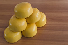 Cow cheese. Yellow shiny cow cheese against a wooden background Royalty Free Stock Images