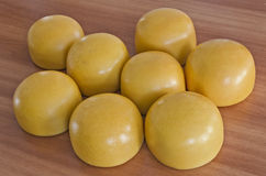 Cow cheese. Yellow shiny cow cheese against a wooden background Royalty Free Stock Image