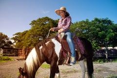 Cow-girl assez asiatique de femme montant un cheval dehors dans une ferme Photographie stock
