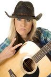 Cow-girl avec la guitare dans le signe de paix bleu de fin de chemise photographie stock