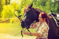 Cow-girl dans la chemise à carreaux étreignant le cheval brun Images stock