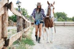 Cow-girl de femme dans le chapeau marchant avec son cheval dans le village Images libres de droits