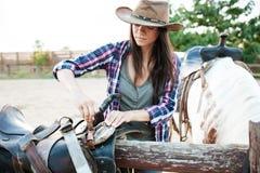 Cow-girl de femme dans le chapeau préparant la selle pour le cheval d'équitation images stock